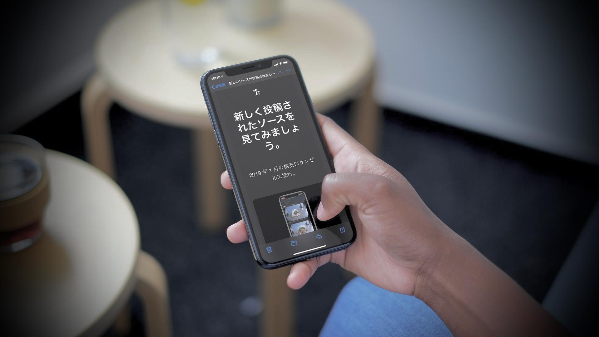 iPhone を手に持っている、画面には Mail Magazine が映し出されている。